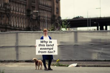 "Zara Kitson stands by derelict land with her dog, holding a sign saying ""Why is this land exempt from tax?"""