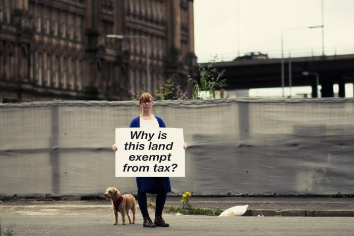 Zara Kitson stands by derelict land with her dog, holding a sign saying